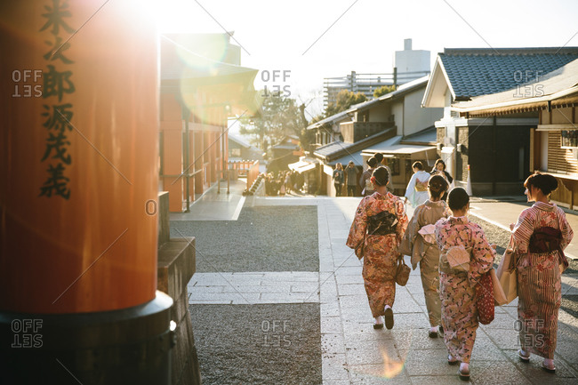 A group of Japanese women dressed in kimono's walking outdoors at sunset