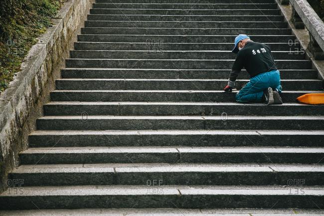 Man repairing a public staircase