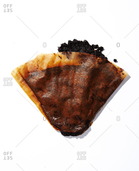 Used coffee filter with coffee grounds on a white seamless background