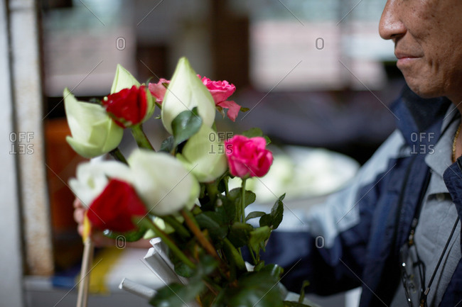 Close-up of a man holding a bouquet of roses
