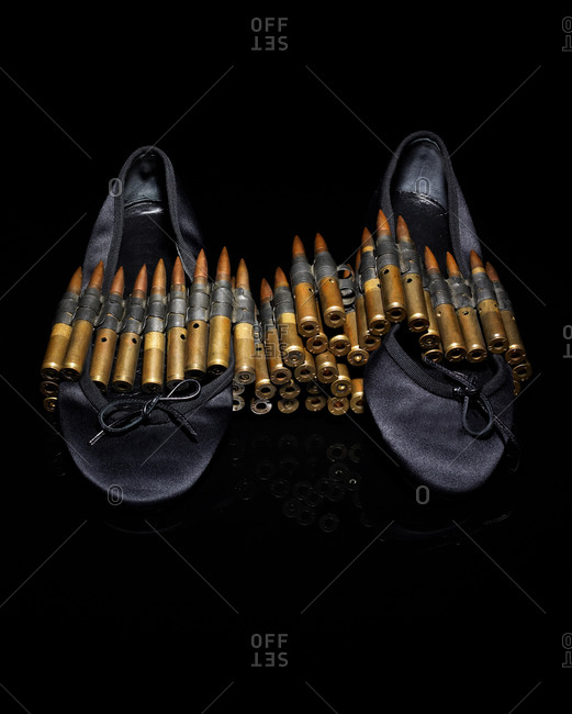 Bullets stacked on top of ballet flats on a dark seamless background