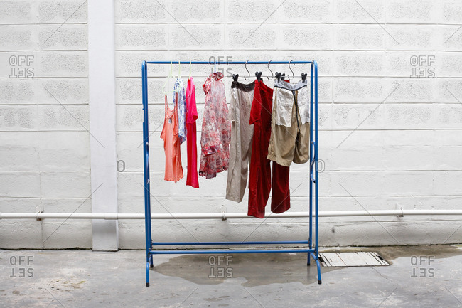 Clothes Hanging On A Rack Outside Along A Cement Wall Stock Photo