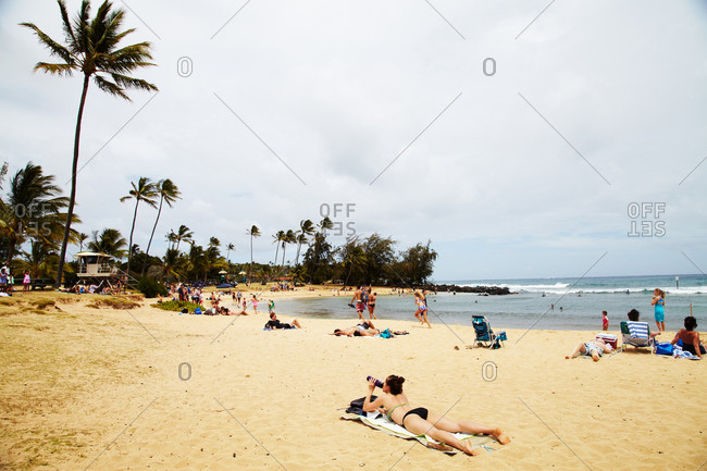 Woman in a bikini lying on Poipu Beach in Kauai drinking from a water bottle