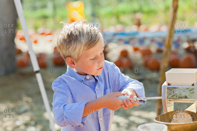 Young boy using a hand grinder outside