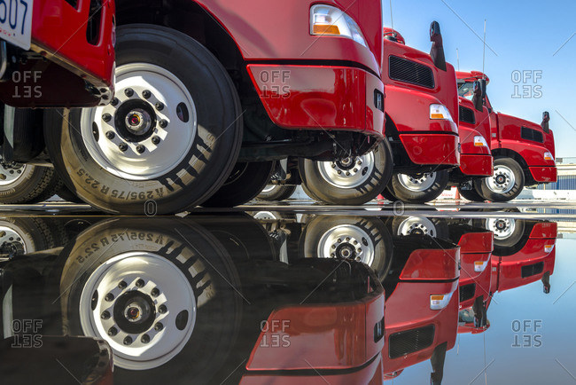 New red tractor trailers parked side-by-side