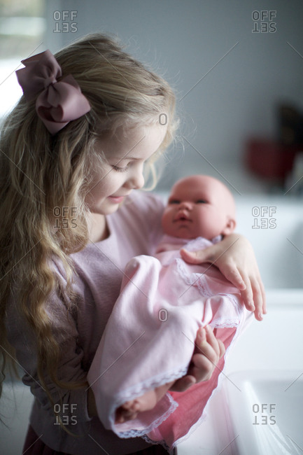 Girl holding baby doll wrapped in a towel