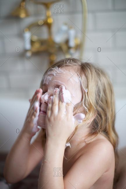 Little girl applying soap on face in a bathtub