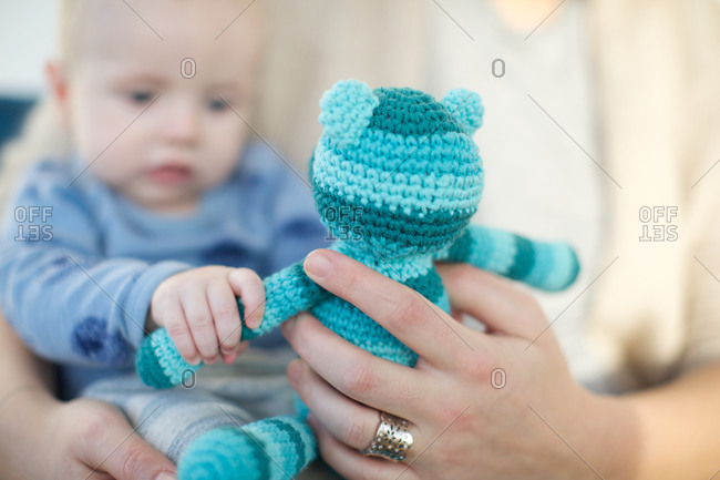 Mother and baby holding knitted soft toy
