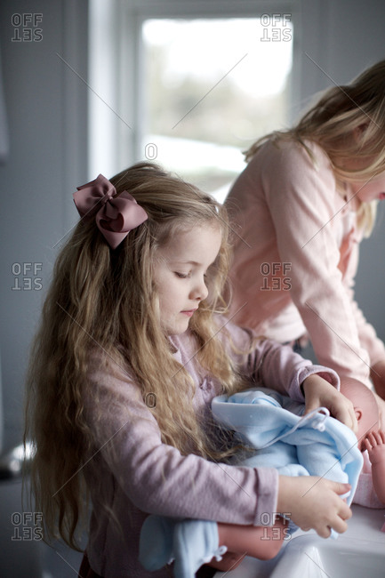 Little girls playing with baby dolls