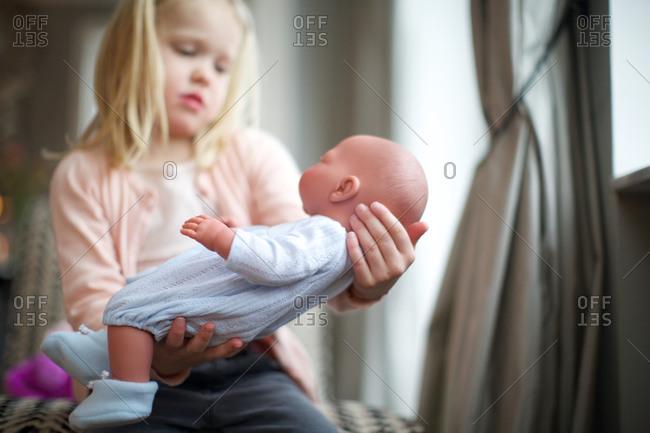 Girl holding baby doll