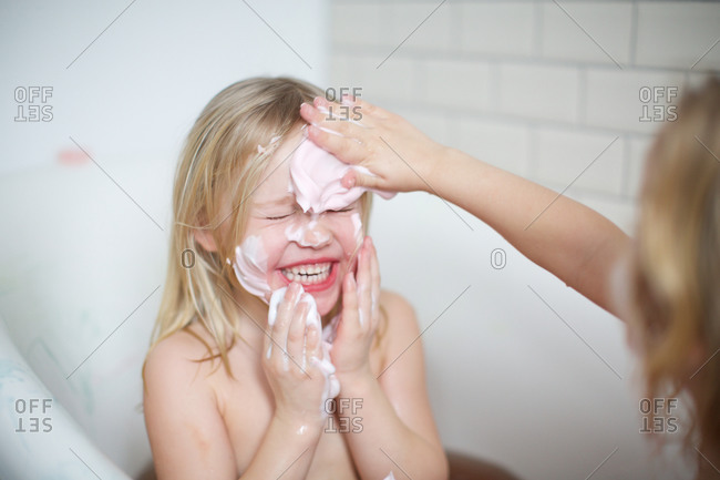 Girl applying soap to sister's face in a bathtub