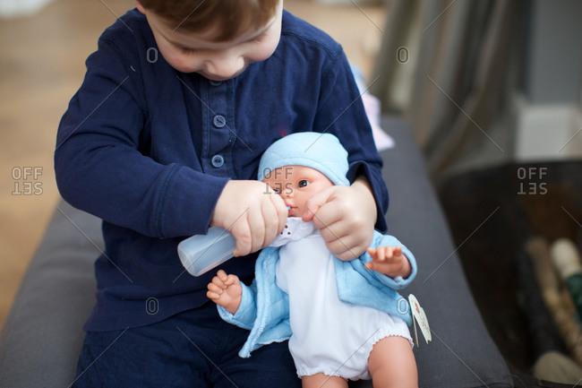 Little boy feeding bottle milk to baby doll
