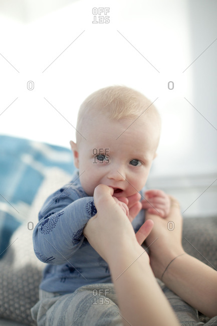 Baby chewing on mother's hands