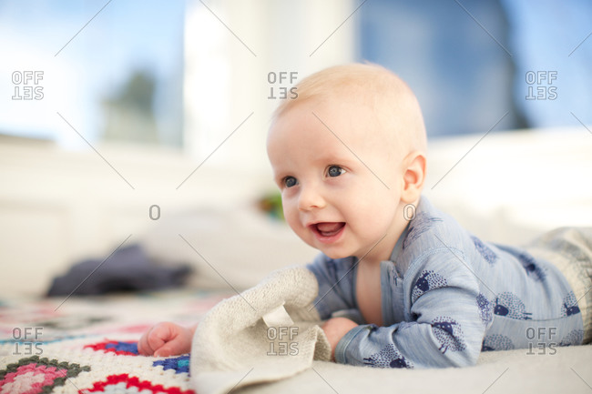 Happy baby boy lying on a bed