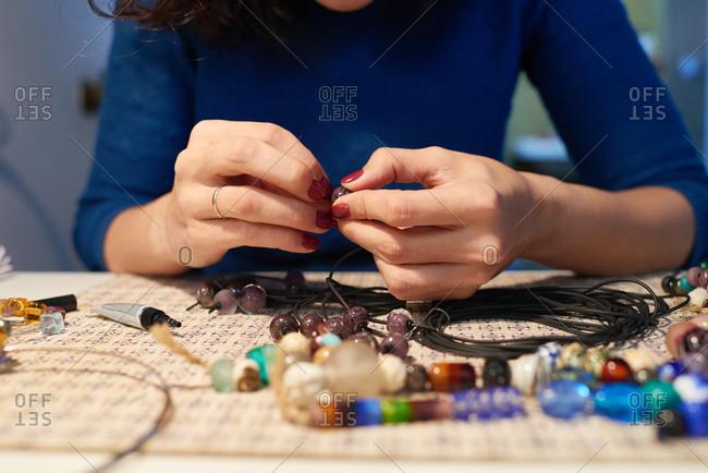 Woman stringing jewelry beads