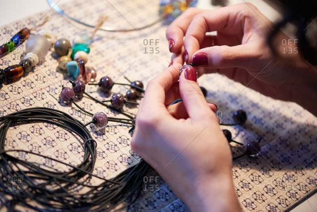 Woman making bead jewelry