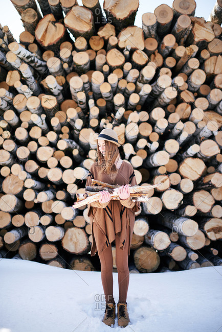 Woman with wood by logs