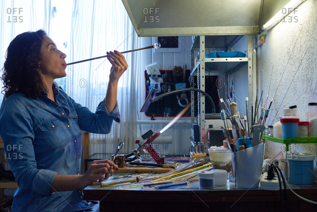 Woman forming bead with blowpipe
