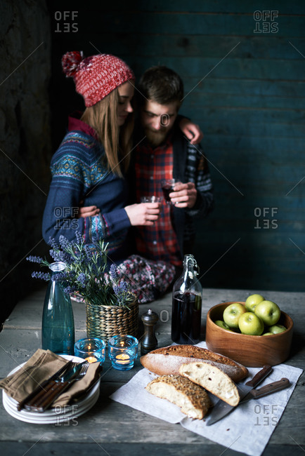 Couple having wine by food table