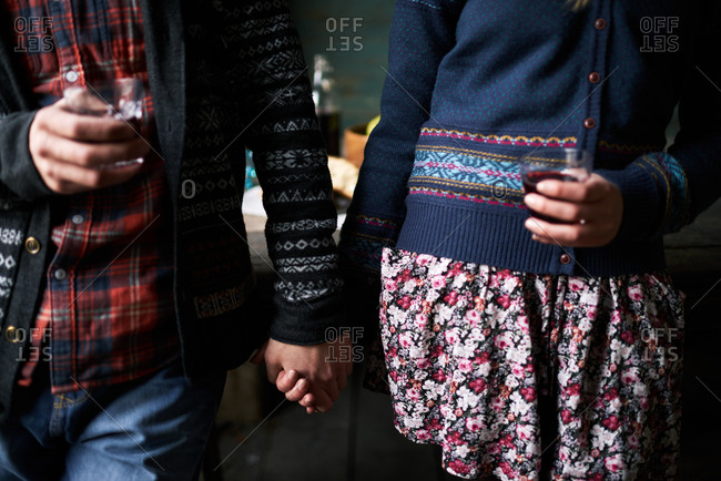 Couple holding hands and wine