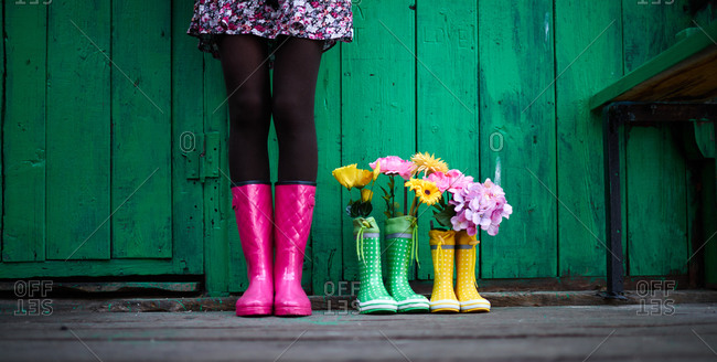 Woman by rain boots with flowers