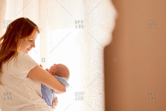 Mom holding newborn by window