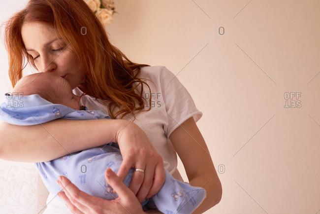 Mom giving newborn loving kiss
