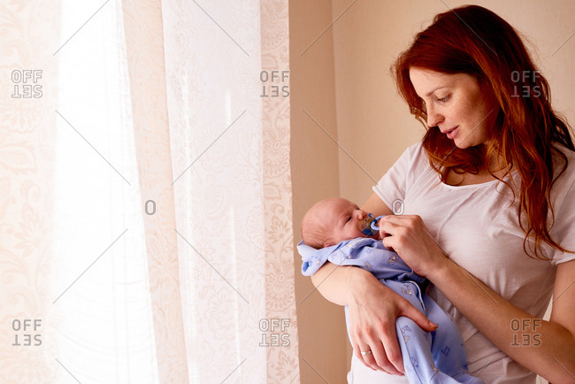 Mom soothing newborn with pacifier