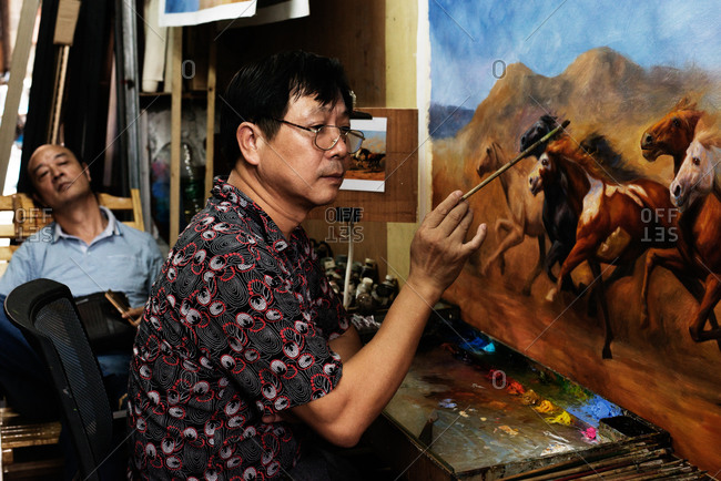 Dafen, China - July 28, 2015: Man painting picture of galloping horses while another man watches