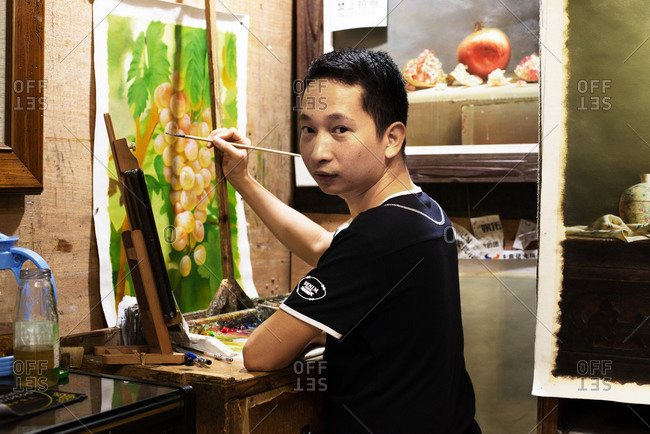 Dafen, China - July 28, 2015: Man painting a bunch of grapes on vine
