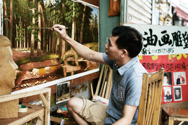 Dafen, China - July 28, 2015: Street artist in China working on a landscape painting