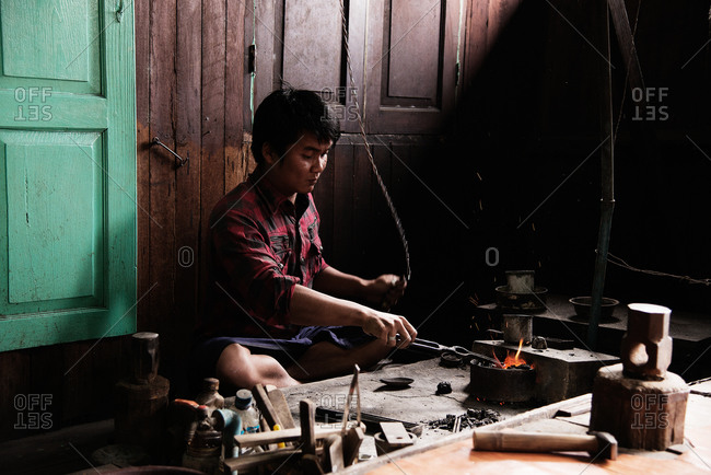 Inle Lake, Myanmar - December 19, 2015: Metalworker heating metal in furnace