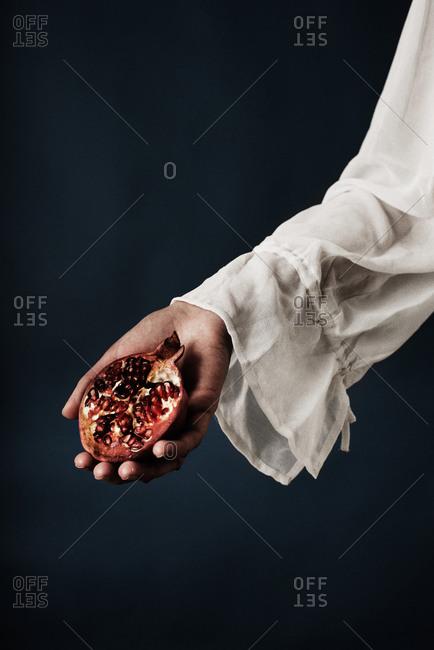 Woman's hand holding a split pomegranate