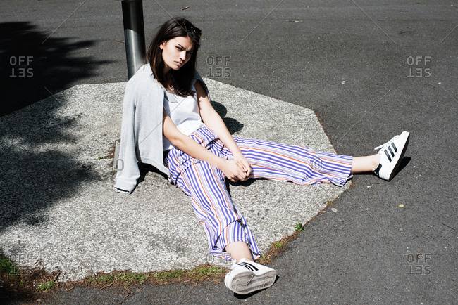 London, United Kingdom - May 21, 2015: Woman in striped trousers sitting on pavement with legs splayed