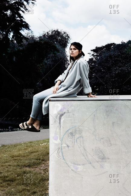 London, United Kingdom - May 21, 2015: Woman sitting on concrete box outdoors