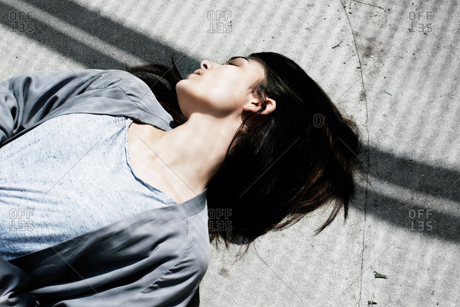 London, United Kingdom - May 21, 2015: Woman lying with head turned on shadow-patterned pavement