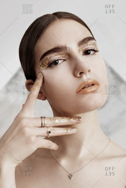 London, United Kingdom - February 13, 2016: Model with gold leaf makeup on her eyes and fingers