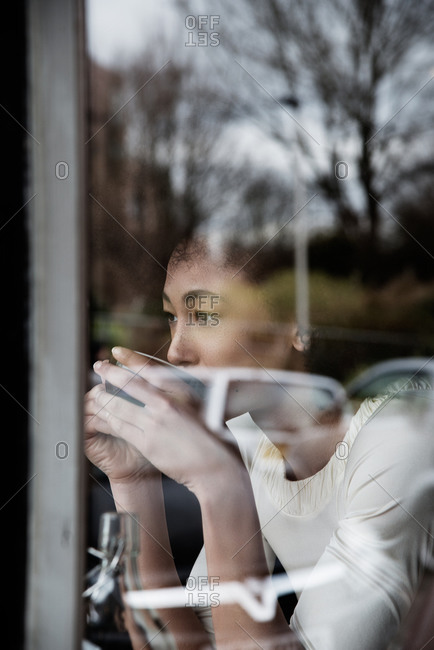 View through window of woman drinking beverage