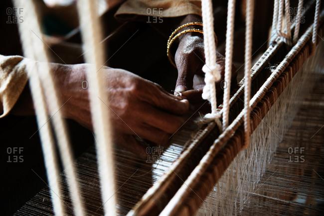 Craftsperson's hands working on textile loom