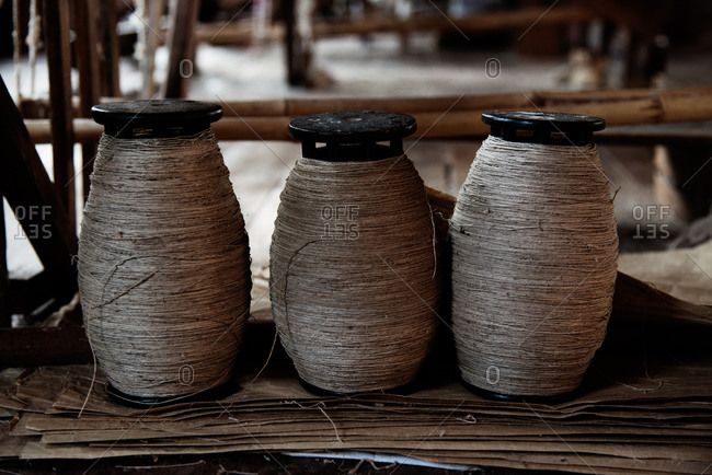 Three spools of natural string in textile mill