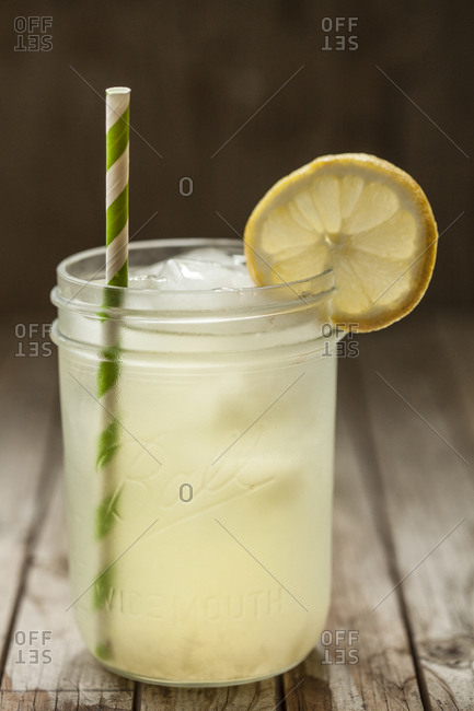 Glass of fresh lemonade with straw on wooden table