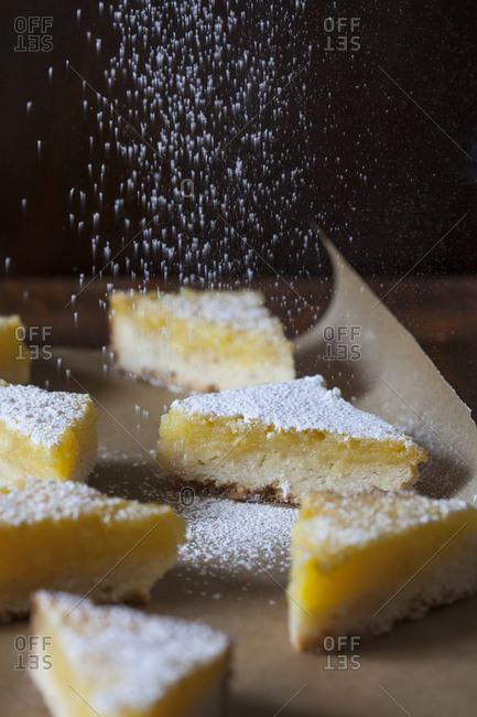 Lemon wedge desserts being dusted with powdered sugar