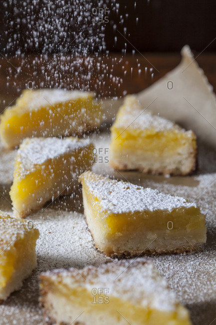 Lemon dessert wedges being sprinkled with powdered sugar