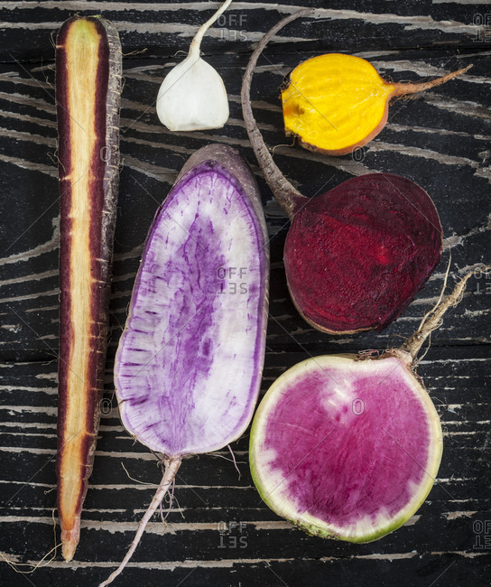 Halved root vegetables on rustic wooden surface