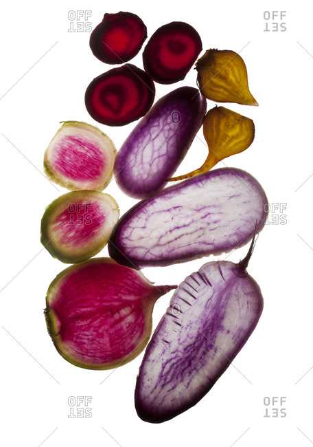 Halved root vegetables on white background