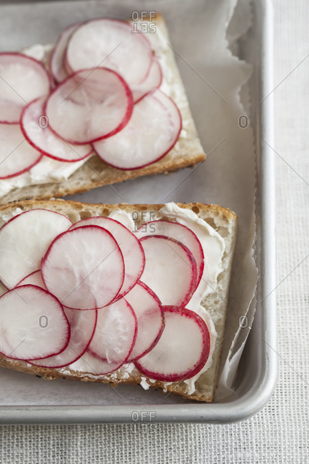Overhead view of bread with cream cheese and sliced radishes