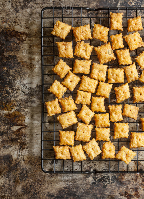 Baked homemade cheese crackers cooking on wire rack