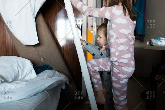 Children climbing up a ladder to a bunk bed on a cruise ship