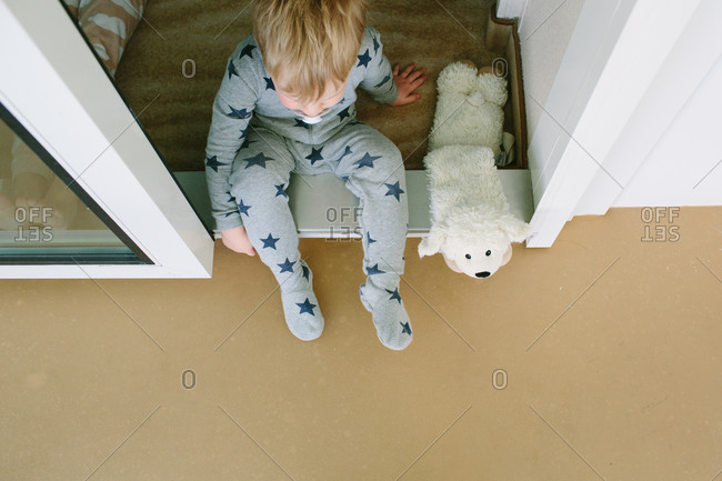 Boy sitting in the doorway to his cabin on a cruise ship
