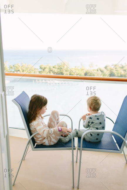 Children sitting in chairs on the deck of a cruise ship